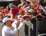 FILE - In this Aug. 3, 2019, file photo, Cleveland Browns quarterback Baker Mayfield, left, gives autographs after the NFL football Orange and Brown Scrimmage, in Cleveland.  Mayfield isn't concerned about the huge expectations being placed on the Browns, who went 7-8-1 during his rookie season but upgraded their roster and should compete for their first playoff spot since 2002. (John Kuntz/The Plain Dealer via AP, File)