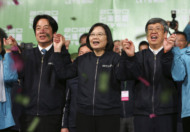 Taiwan's 2020 presidential election candidate, Taiwanese President Tsai Ing-wen, center, anf her running mate William Lai, left, celebrate their victory with supporters in Taipei, Taiwan, Saturday, Jan. 11, 2020.  Taiwan's independence-leaning President Tsai Ing-wen won a second term in a landslide election victory Saturday, signaling strong support for her tough stance against China. (AP Photo/Chiang Ying-ying)