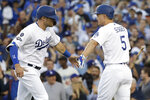 Los Angeles Dodgers' A.J. Pollock, left, celebrates with Corey Seager after scoring on a bases-loaded walk during the first inning of Game 1 in baseball's National League Divisional Series against the Washington Nationals on Thursday, Oct. 3, 2019, in Los Angeles. (AP Photo/Marcio Jose Sanchez)