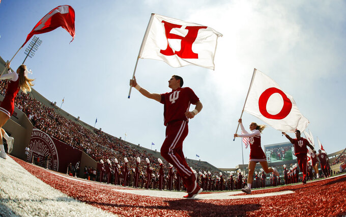 Indiana cheerleaders carry flags before an NCAA college football game against Ball State, Saturday, Sept. 15, 2018 in Bloomington, Ind. (Jeremy Hogan/The Herald-Times via AP)