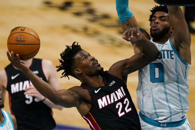 Miami Heat forward Jimmy Butler shoots over Charlotte Hornets forward Miles Bridges during the first half of an NBA basketball game on Sunday, May 2, 2021, in Charlotte, N.C. (AP Photo/Chris Carlson)