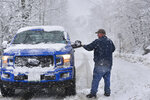 Robert Clark, of Marlboro, Vt., clears the snow off his vehicle on Augur Hole Road, in Marlboro, Vt., before turning onto Route 9 as several inches of snow falls on Friday, April 16, 2021. (Kristopher Radder/The Brattleboro Reformer via AP)