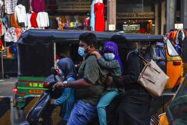 An Indian family wearing face masks as a precaution against the coronavirus rides on a scooter through a street in Hyderabad, India, Wednesday, Dec. 9, 2020. India has more than 9 million cases of coronavirus, second behind the United States. (AP Photo/Mahesh Kumar A.)