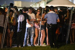 In this  Saturday, Sept. 7, 2019 photo, Festival-goers talk to a police officer after they try to jump the fence during Lil Wayne's fifth annual Lil WeezyAna Fest at the UNO Lakefront Arena grounds in New Orleans. A crowd stampede injured several people attending a New Orleans festival organized by rapper Lil Wayne. (Sophia Germer/The Advocate via AP)