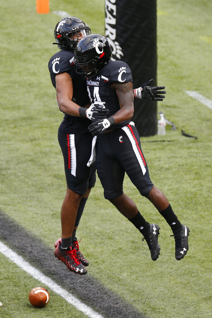Cincinnati running back Jerome Ford, right, celebrates his touchdown against Army with teammate Leonard Taylor during the second half of an NCAA college football game Saturday, Sept. 26, 2020, in Cincinnati, Ohio. Cincinnati beat Army 24-10. (AP Photo/Jay LaPrete)