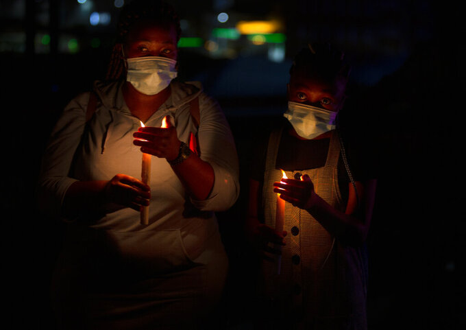 Frontline workers attend a candlelight ceremony on New Year's Eve on the famed Nelson Mandela Bridge in downtown Johannesburg Thursday, Dec. 31, 2020. Many South Africans will swap firecrackers for candles to mark New Year's Eve amid COVID-19 restrictions including a nighttime curfew responding to President Cyril Ramaphosa's call to light a candle to honor those who have died in the COVID-19 pandemic and the health workers who are on the frontline of battling the disease. (AP Photo/Denis Farrell)