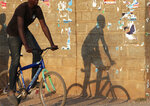 A boy is silhouetted as he rides his bicycle past torn down election posters on the streets of Lusaka, Zambia, Tuesday, Aug, 17, 2021. Business quickly returned to normal in Zambia Tuesday, a day after veteran opposition leader Hakainde Hichilema was declared president -elect and the incumbent president Edgar Lungu conceded his election defeat.(AP Photo/Tsvangirayi Mukwazhi)
