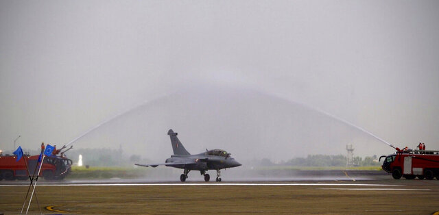 Water is sprayed on a French-made Rafale fighter jet during its induction ceremony at the Indian Air Force Station in Ambala, India, Thursday, Sept.10, 2020. The first batch of five planes, part of a $8.78 billion deal signed between the two countries in 2016 had arrived here in July. (AP Photo/Manish Swarup)