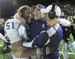 FILE - In this Dec. 18, 2010, file photo, Carroll College coach Mike Van Diest, center, is hugged by linebacker Lynn Mallory (51) and another coach after Carroll College defeated Sioux Falls in the NAIA college football championship game at Brannon Field in Rome, Ga. Van Diest announced his retirement Monday, Nov. 12, 2018, after 20 seasons and six NAIA national championships at the Helena school. (AP Photo/Erik S. Lesser, file)