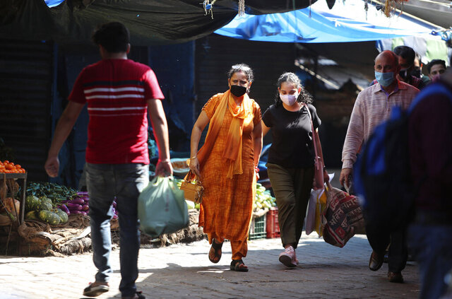 Indians wearing a face masks as a precaution against the coronavirus walk at a vegetables market in Jammu, India, Wednesday, Sept.23, 2020. The nation of 1.3 billion people is expected to become the pandemic's worst-hit country within weeks, surpassing the United States. (AP Photo/Channi Anand)