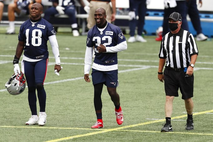 New England Patriots wide receiver Matthew Slater (18) and defensive back Devin McCourty (32) walk to center field before an NFL football training camp scrimmage, Friday, Aug. 28, 2020, in Foxborough, Mass. (AP Photo/Michael Dwyer, Pool)