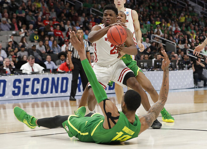 Wisconsin guard Khalil Iverson (21) holds the ball over Oregon forward Kenny Wooten (14) during the second half of a first round men's college basketball game in the NCAA Tournament, Friday, March 22, 2019, in San Jose, Calif. (AP Photo/Chris Carlson)