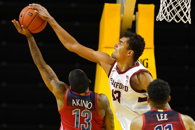 Stanford forward Oscar da Silva, right, defends a shot by Arizona guard James Akinjo during the second half of an NCAA college basketball game in Santa Cruz, Calif., Saturday, Dec. 19, 2020. (AP Photo/Jeff Chiu)