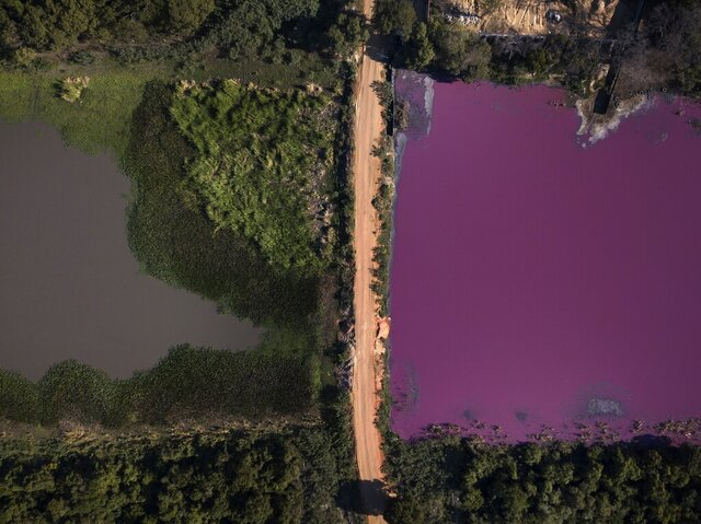 A road divides the Cerro Lagoon, where the water at right is colored and the Waltrading S.A. tannery stands on the bank, top right, in Limpio, Paraguay, Wednesday, Aug. 5, 2020. According to Francisco Ferreira, a technician at the National University Multidisciplinary Lab. who is taking water samples at the site on Wednesday, the color of the water is due to the presence of heavy metals like chromium, commonly used in the tannery process. (AP Photo/Jorge Saenz)