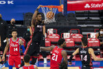Miami Heat's Chris Silva, center left, dunks the ball with Philadelphia 76ers' Joel Embiid, center right, defending during the first half of an NBA basketball game, Thursday, Jan. 14, 2021, in Philadelphia. (AP Photo/Chris Szagola)