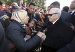 Tunisian President Beji Caid Essebsi shake hands with bystanders as he arrives for a event in Tunis, Tunisia, Sunday, Jan. 14, 2018. Tunisian authorities announced plans to boost aid to the needy in a bid to placate protesters whose demonstrations over price hikes degenerated into days of unrest across the North African nation, which is marking seven years on Sunday since its long-time autocratic ruler was driven into exile.(Slim Abid/Tunisian Presidency via AP)