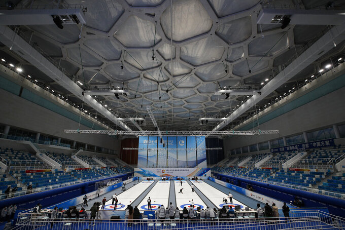 "Local team players compete in a curling competition during a test event for the 2022 Beijing Winter Olympics at National Aquatic Center, also known as the ""Water Cube"" in Beijing, Thursday, April 1, 2021. Chinese capital hold a 10 days test events for 2022 Beijing Winter Olympics in five different venues from April 1-10, becomes the first city to hold both the Winter and Summer Olympics. (AP Photo/Andy Wong)"