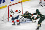 Florida Panthers defenseman Keith Yandle (3) shoots the puck past Minnesota Wild goalie Alex Stalock, center, to score as Minnesota Wild winger Kevin Fiala (22) reaches in to block the shot to during the first period of an NHL hockey game Monday, Jan. 20, 2020, in St. Paul, Minn. (AP Photo/Craig Lassig)