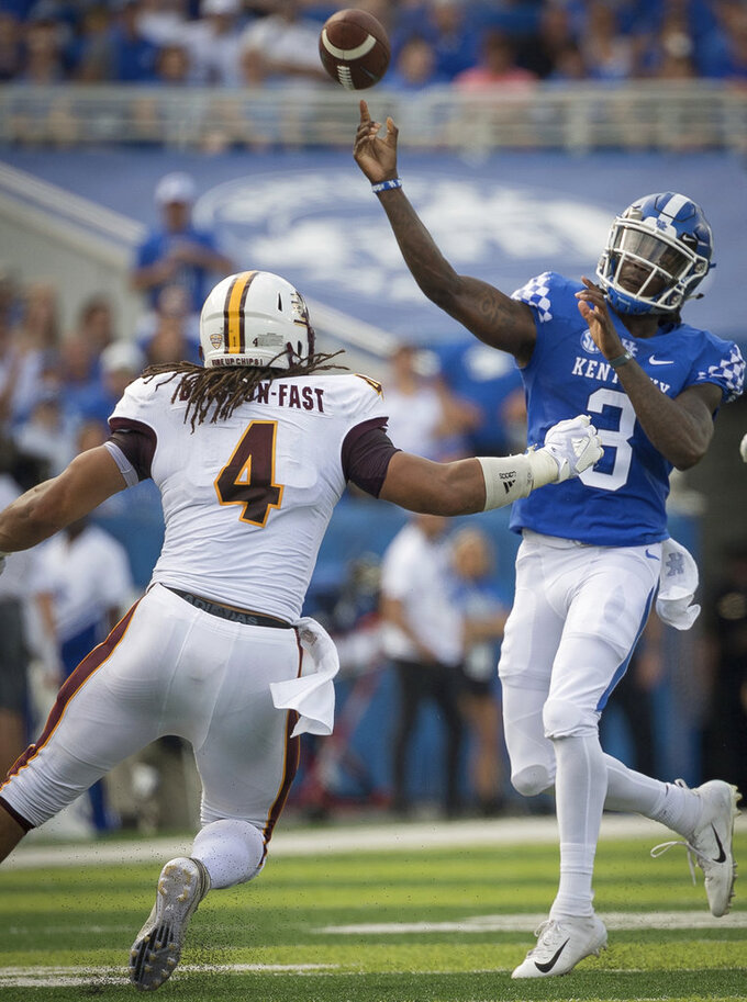 Kentucky quarterback Terry Wilson (3) passes the ball over Central Michigan defensive lineman Nate Brisson-Fast during the first half of an NCAA college football game in Lexington, Ky., Saturday, Sept. 1, 2018. (AP Photo/Bryan Woolston)