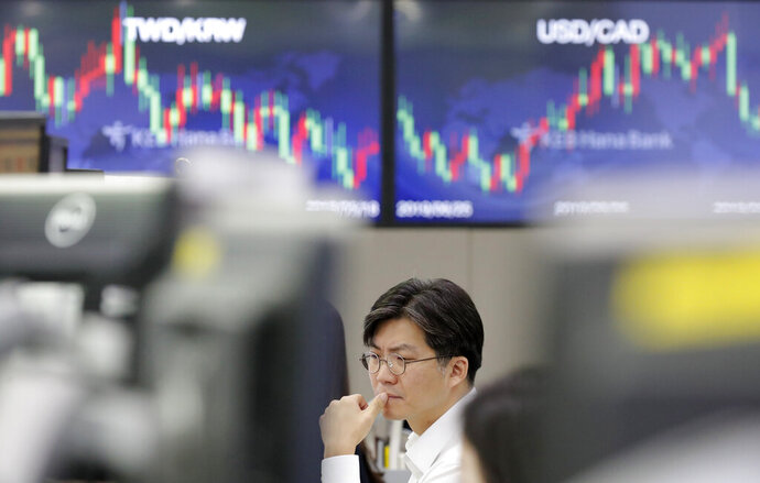 A currency trader watches the computer monitors near the screens showing the foreign exchange rates at the foreign exchange dealing room in Seoul, South Korea, Monday, Sept. 16, 2019. An attack on a critical Saudi Arabia oil plant has pushed crude prices sharply higher, though they moderated on expectations that reserves will help bridge any shortfalls in output.(AP Photo/Lee Jin-man)
