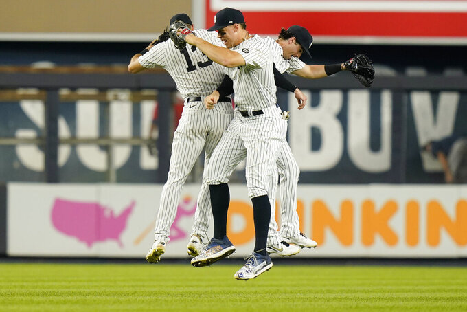 New York Yankees' Aaron Judge, center, Joey Gallo, left, and Tyler Wade, right, celebrate after a baseball game against the Minnesota Twins, Friday, Aug. 20, 2021, in New York. (AP Photo/Frank Franklin II)
