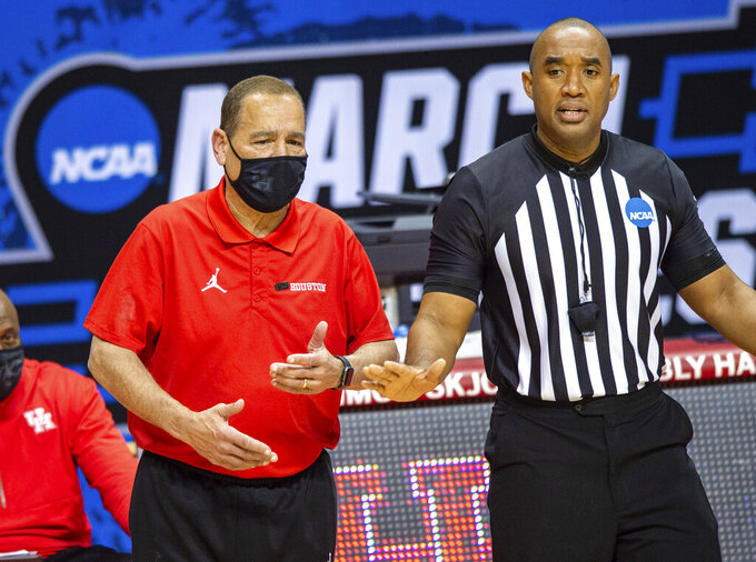 Houston head coach Kelvin Sampson talks with a game official during the second half of a first-round game against Cleveland State in the NCAA men's college basketball tournament, Friday, March 19, 2021, at Assembly Hall in Bloomington, Ind. (AP Photo/Doug McSchooler)