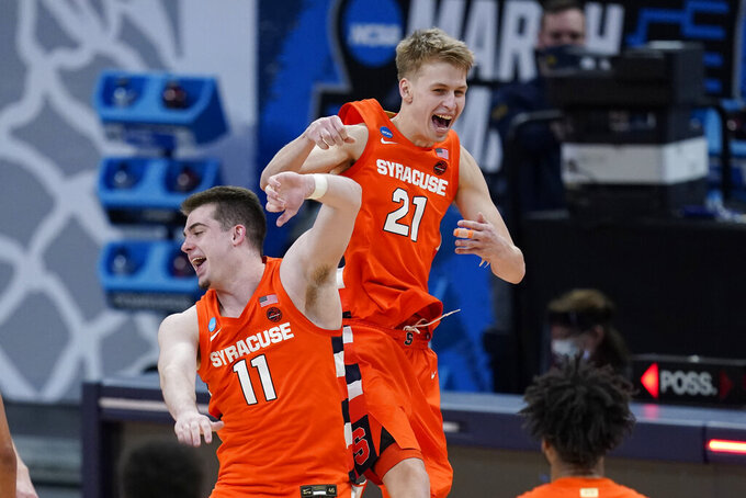 Syracuse's Joseph Girard III (11) and Marek Dolezaj (21) celebrate following a second-round game against West Virginia in the NCAA men's college basketball tournament at Bankers Life Fieldhouse, Sunday, March 21, 2021, in Indianapolis. Syracuse defeated Syracuse 75-72. (AP Photo/Darron Cummings)