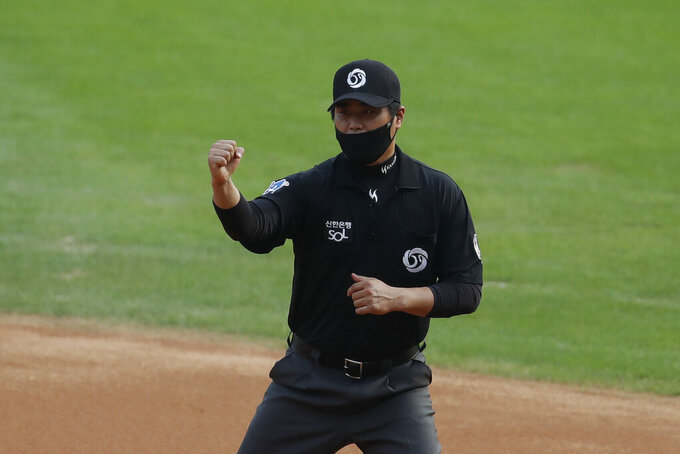 First base umpire Kim Seon-soo, wearing a mask as a precaution against the coronavirus, makes a call during the KBO league baseball game between KT Wiz and Doosan Bears in Seoul, South Korea, Sunday, Aug. 16, 2020. Fans are banned once again from professional baseball and soccer games, which had just begun to slowly bring back spectators in late July. (AP Photo/Lee Jin-man)