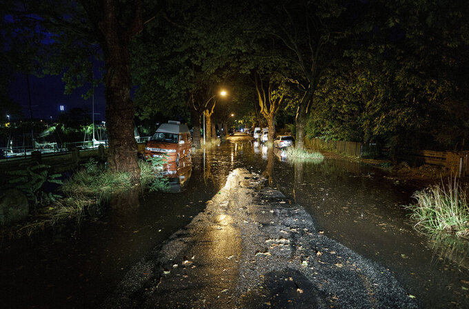 Thunderstorms and heavy rain showers pass over the district of Holtenau, in Kiel, Germany, where a street is underwater, on Monday, July 26, 2021. (Axel Heimken/dpa via AP)