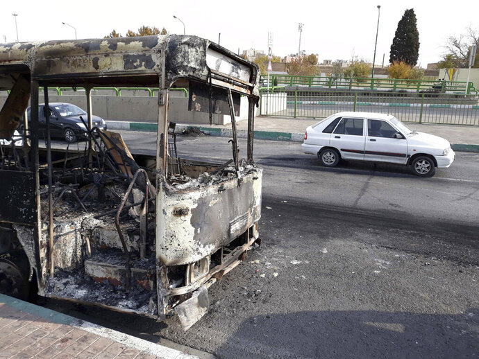 This photo released by the Iranian Students' News Agency, ISNA, shows cars drive past a scorched public bus that remained on the street after protests that followed authorities' decision to raise gasoline prices, in Tehran, Iran, Sunday, Nov. 17, 2019.  Ayatollah Ali Khamenei, Iran's supreme leader, on Sunday backed the government's decision to raise gasoline prices and called angry protesters who have been setting fire to public property over the hike