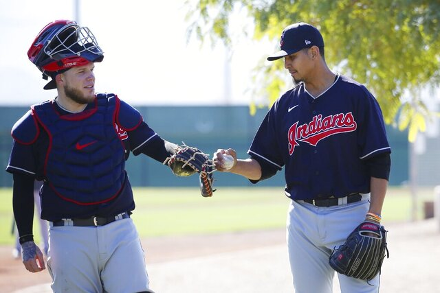 Cleveland Indians starting pitcher Carlos Carrasco, right, taps the glove of catcher Roberto Perez, left, after a pitching session during spring training baseball workouts for pitchers and catchers Thursday, Feb. 13, 2020, in Avondale, Ariz. (AP Photo/Ross D. Franklin)