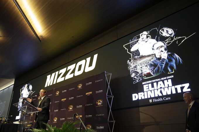 Eliah Drinkwitz speaks at a podium as he is introduced as the new NCAA college football head coach at the University of Missouri, Tuesday, Dec. 10, 2019, in Columbia, Mo. Drinkwitz becomes the 33rd head football coach at Missouri after coaching the 2019 season at Appalachian State. (AP Photo/Jeff Roberson)