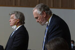 Bill Johnson, chief executive officer and president of PG&E Corp., right, lowers his head after admitting the company's guilt in the deaths of 84 people in a 2018 wildfire, during a hearing in Butte County Superior Court in Chico, Calif., Tuesday, June 16, 2020. Johnson entered guilty pleas on behalf of the company for 84 felony counts of involuntary manslaughter stemming from the fire which was blamed on the company's crumbling electrical grid the wiped out the town of Paradise in November of 2018.(AP Photo/Rich Pedroncelli, Pool)
