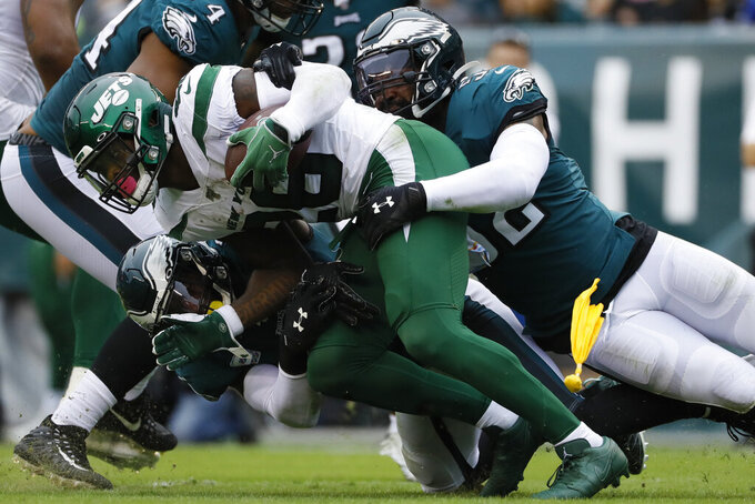 New York Jets' Le'Veon Bell, center, is tackled by Philadelphia Eagles' Malcolm Jenkins, left, and Zach Brown during the first half of an NFL football game, Sunday, Oct. 6, 2019, in Philadelphia. (AP Photo/Michael Perez)