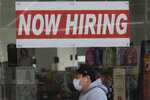FILE - This May 7, 2020, file photo shows a man wearing a mask while walking under a Now Hiring sign at a CVS Pharmacy during the coronavirus outbreak in San Francisco. At least 350,000 debit cards filled with money for unemployment benefits in California have been frozen because of suspected fraud.  (AP Photo/Jeff Chiu, File)
