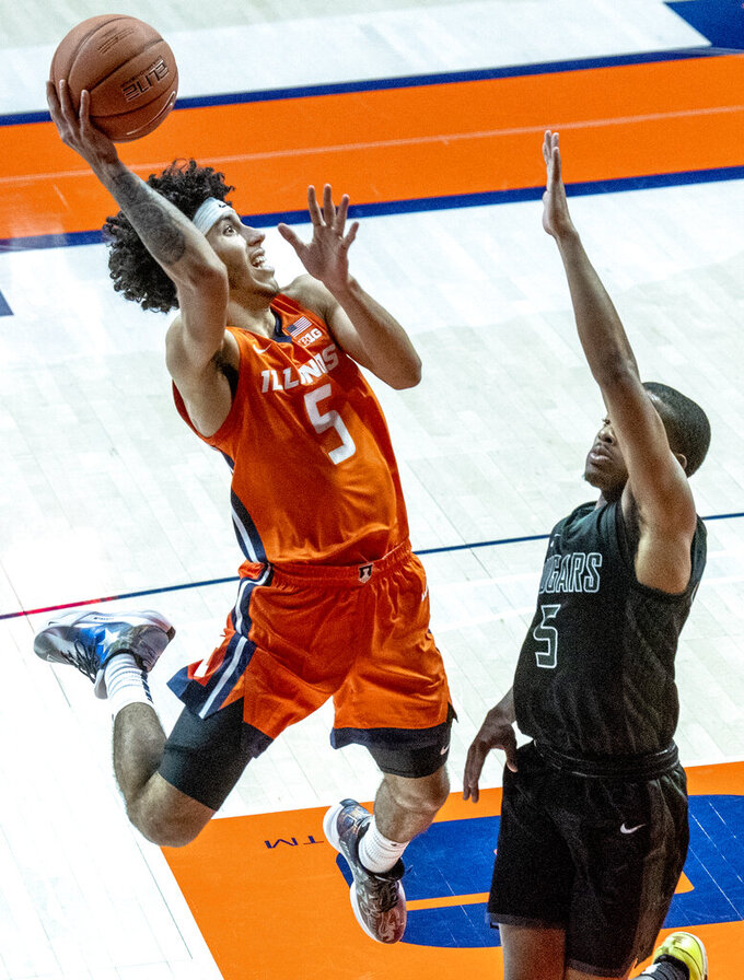 Illinois guard Andre Curbelo (5) shoots over Chicago State's guard Xavier Johnson (5) during the second half of an NCAA college basketball game in Champaign, Ill., Thursday, Nov. 26, 2020. (Robin Scholz/The News-Gazette via AP)