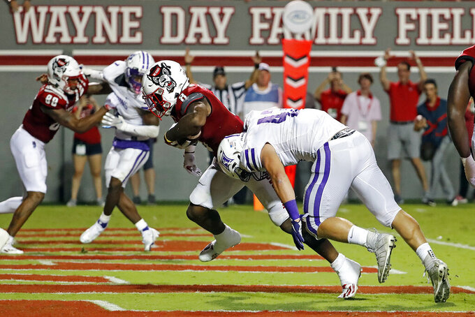 North Carolina State's Ricky Person Jr. (8) runs the ball into the end zone past Furman's Braden Gilby (43) during the second half of an NCAA college football game in Raleigh, N.C., Saturday, Sept. 18, 2021. (AP Photo/Karl B DeBlaker)