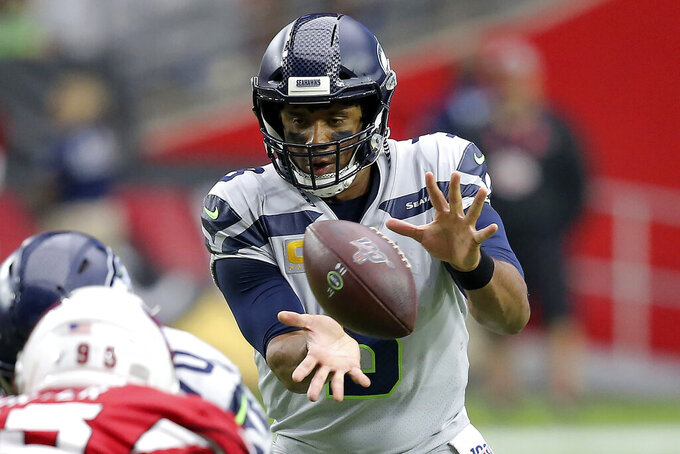 Seattle Seahawks quarterback Russell Wilson takes the snap against the Arizona Cardinals during the first half of an NFL football game, Sunday, Sept. 29, 2019, in Glendale, Ariz. (AP Photo/Ross D. Franklin)