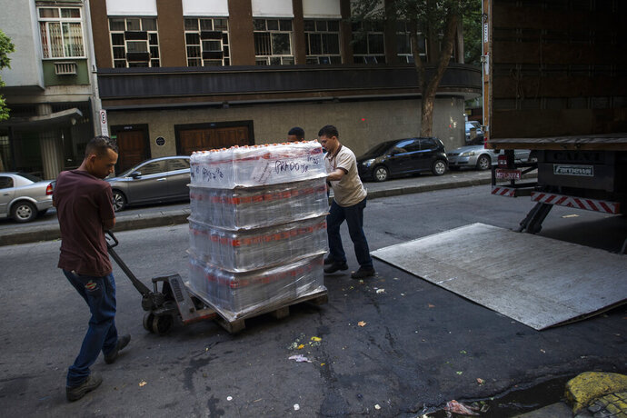 Workers move bottled water to be sold at a supermarket in the Copacabana neighborhood of Rio de Janeiro, Brazil, Wednesday, Jan. 15, 2020. There's a creeping sense of alarm in Rio de Janeiro after more than a week of foul tasting and smelling tap water in dozens of neighborhoods, and residents are hoarding bottled water. (AP Photo/Bruna Prado)