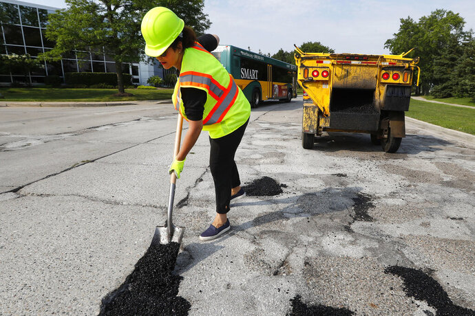 FILE- In an Aug. 6, 2018 file photo, then-Michigan Democratic gubernatorial candidate Gretchen Whitmer fills a pothole during a campaign event in Southfield, Mich. Gov. Whitmer is expected make roads a focus in her Jan. 29, 2020, State of the State speech after Republicans lawmakers last year rejected a proposed 45-cents-a-gallon fuel tax hike phased in over a year. Whitmer has signaled that it may take pursuing a number of revenue-raising options given the