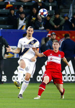 LA Galaxy forawrd Zlatan Ibrahimovic, left, of Sweden, kicks the ball away from Chicago Fire midfielder Bastian Schweinsteiger of Germany in the first half of an MLS soccer match in Carson, Calif., Saturday, March 2, 2019. (AP Photo/Ringo H.W. Chiu)