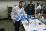 Guatemalan President Jimmy Morales looks to photographers as he casts his vote during a plebiscite on a border dispute with Belize, in Guatemala City, Sunday, April 15, 2018. Guatemalans are deciding whether their government should request the International Court of Justice to resolve the dispute that dates back to 1821 when Guatemala won independence from Spain and its border with the United Kingdom's territory was being decided. Guatemala recognized Belize's independence in 1992 but did not recognize its border. (AP Photo/Moises Castillo)