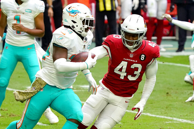 Miami Dolphins running back Jordan Howard (34) runs the ball as Arizona Cardinals outside linebacker Haason Reddick (43) defends during the first half of an NFL football game, Sunday, Nov. 8, 2020, in Glendale, Ariz. (AP Photo/Rick Scuteri)