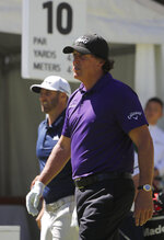 Phil Mickelson, right, and Dustin Johnson, walk on the tenth hole during the first day of competition of the WGC-Mexico Championship at the Chapultepec Golf Club in Mexico City, Thursday, Feb. 21, 2019. (AP Photo/Marco Ugarte)