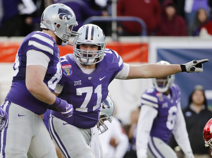 FILE - In this Jan. 2, 2016, file photo, Kansas State offensive lineman Dalton Risner (71) gestures at the line of scrimmage during the first half of the Liberty Bowl NCAA college football game  against Arkansas in Memphis, Tenn. Risner has a future in the NFL. But he also hopes his future includes the growth and development of his foundation, RiseUp, which aims to provide hope and inspire young people. Eventually, he wants to establish a series of football-centric summer camps for kids that come from a variety of backgrounds.  (AP Photo/Mark Humphrey, File)