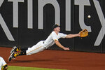 Pittsburgh Pirates left fielder Bryan Reynolds dives for but can't come up with a fly ball hit by Los Angeles Dodgers' Mookie Betts for an RBI triple during the fifth inning of a baseball game in Pittsburgh, Tuesday, June 8, 2021. (AP Photo/Gene J. Puskar)