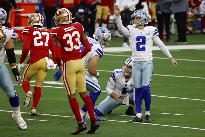 Dallas Cowboys' Hunter Niswander (1) and Greg Zuerlein (2) watch Zuerlein's field goal go through the uprights as San Francisco 49ers' Dontae Johnson (27) and Tarvarius Moore (33) rush on the play in the second half of an NFL football game in Arlington, Texas, Sunday, Dec. 20, 2020. (AP Photo/Ron Jenkins)