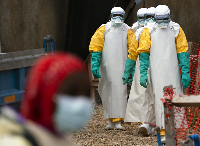 FILE - In this Tuesday, July 16, 2019 file photo, health workers dressed in protective gear begin their shift at an Ebola treatment center in Beni, Congo DRC. The World Health Organization says the ongoing Ebola outbreak in Congo still warrants being classified as a global emergency, even though the number of confirmed cases has slowed in recent weeks. (AP Photo/Jerome Delay, File)