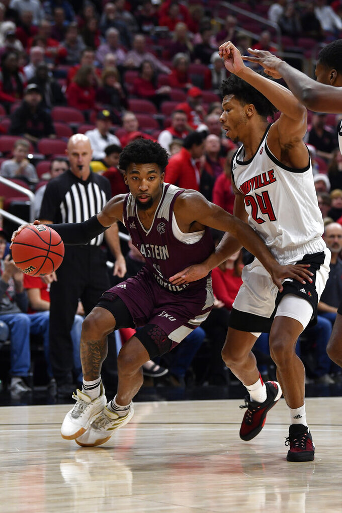 Eastern Kentucky guard Jomaru Brown (11) attempts to drive around the defense of Louisville forward Dwayne Sutton (24) during the first half of an NCAA college basketball game in Louisville, Ky., Saturday, Dec. 14, 2019. (AP Photo/Timothy D. Easley)