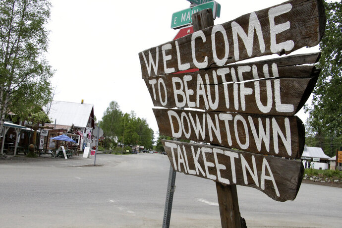 In this June 2, 2020, photo streets in downtown Talkeetna, Alaska are nearly empty. Normally a bustling tourist town, things this summer are pretty quiet in Talkeetna after most major cruise ship companies have canceled their summer tourist seasons because of the coronavirus pandemic. As a result nearly half of Alaska's annual 2.2 million visitors won't be visiting the nation's northernmost state. (AP Photo/Mark Thiessen)